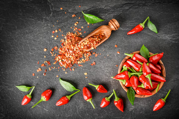 Canvas Prints Hot chili peppers Red hot peppers in wooden bowl on dark stone table. Chili small pepper seeds in scoop and green leaves on black background top view.