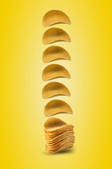 Potato crisps falling down against a yellow background with copy space for text or images. Crispy, palatable chips. Advertising. Close-up.