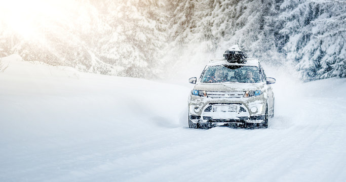 CORTINA D'AMPEZZO, ITALY - JANUARY 31, 2019: Winter roads in beatiful snowy forest. Snow calamity or blizzard on street. Fast modern suzuki Vitara car on snow road in storm.