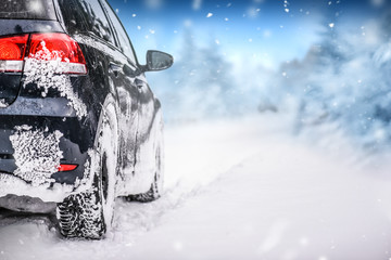 Car in winter on snowy road. Speed snow cars background with mountains.