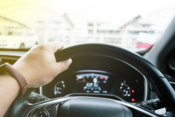 Young man hand holding on the steering wheel and driving a car with blur background