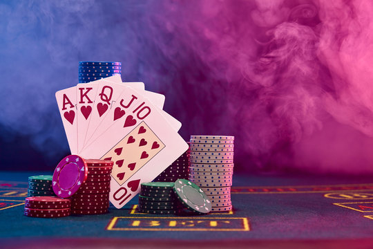 Winning combination in poker leaning on colored chips piles on blue cover of playing table. Black, smoke background, red and blue backlights. Casino.