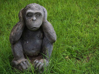 Monkey statue close ears with natural grass green background.