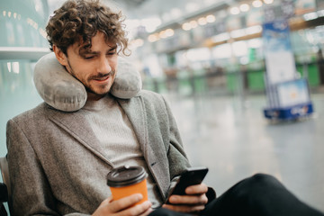 Picture of young man in suit sitting in waiting room and use phone in hands. Wait for train or airplane. Hold cup of coffee in hands. Pillow around neck. Calm and concentrated. Manager travel abroad.