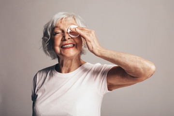 Old but happy positive and cheerful old female model posing on camera. Hold white sponge in hand and cover one eye with it. Cheerful smile. Isolated oer brown background.