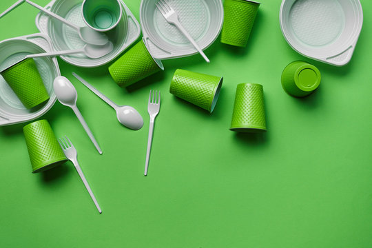White plastic disposable tableware on green background with copy space. The concept of picnic utensil. Top view. Selective focus. Close-up.