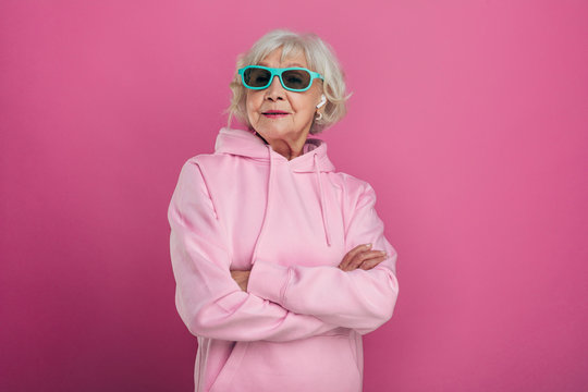 Cool old woman in funny green sunglasses posing on camera. Hands crossed. Wear pink hoody. Stylish modern grandma. Isolated over pink background.