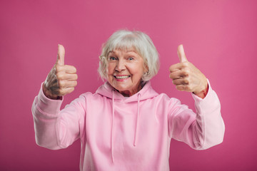 Positive senior model show big thumbs up. Stand alone and pose on camera. Wear pink sweater. Old woman wear modern clothes. Isolated over pink background.