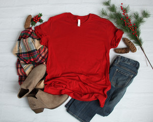 Flat lay mock-up of red t-shirt with Christmas holiday accessories