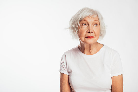 Sad, serious and concentrated old woman sit alone and look to side. Calm, peaceful elder model with grey hair. Wear white shirt. Alone inside. Isolated over white background.