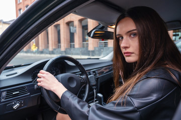 a young woman sits in her car in the Parking lot. On young girl leather women black color of. Concept of girl with character and dangerous driving.