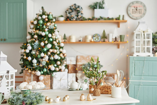 Christmas decor in kitchen. Christmas tableware. Christmas cooking utensils. Bright interior of New Year's cuisine. New Year card template. White Mint Colors Kitchen. Christmas tree in the kitchen.