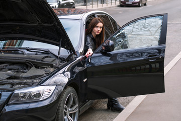 a young woman sits in her car in the Parking lot. On young girl leather women black color of. young woman in her car in the Parking lot. the car's hood is open. the car broke down. Concept of girl