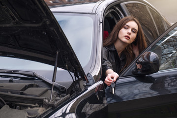 a young woman sits in her car in the Parking lot. On young girl leather women black color of. in the hands of a woman the key to the lock of the car. Concept of girl with character and dangerous