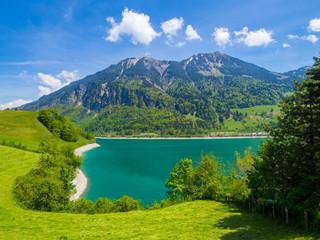 Berge mit tiefblauem See und Strand in der Schweiz (Lungenersee)