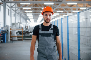 Going forward. Industrial worker indoors in factory. Young technician with orange hard hat