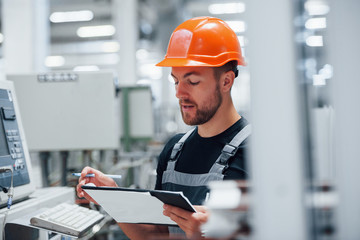Making notes. Industrial worker indoors in factory. Young technician with orange hard hat