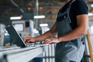 Modern laptop. Typing on keyboard. Industrial worker indoors in factory. Young technician with orange hard hat