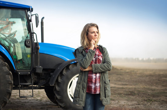 Pensive woman near the tractor on the background of the field.