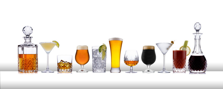 A line of aclcoholic drinks from whisky to lager, in a line, on a white bar like surface