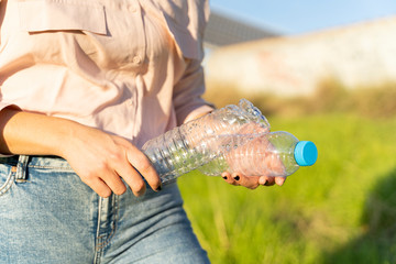 Woman's hands holding empty plastic bottles, close-up