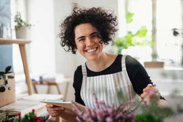 Portrait of happy young woman with clipboard in a small shop with plants