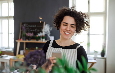 Smiling young woman taking smartphone picture of flowers in a small shop