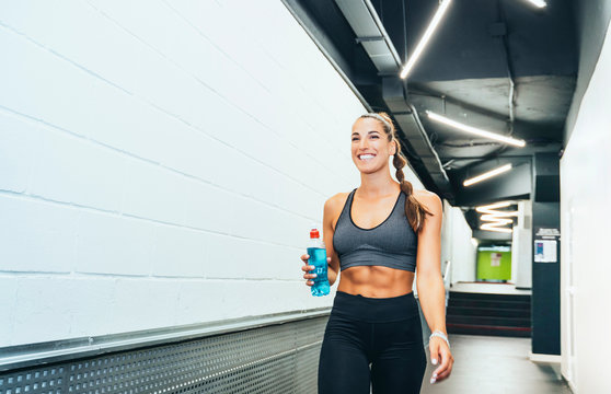 Smiling woman in good shape walking through corridor during workout with water bottle