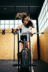 Athletic woman doing air bike workout at gym
