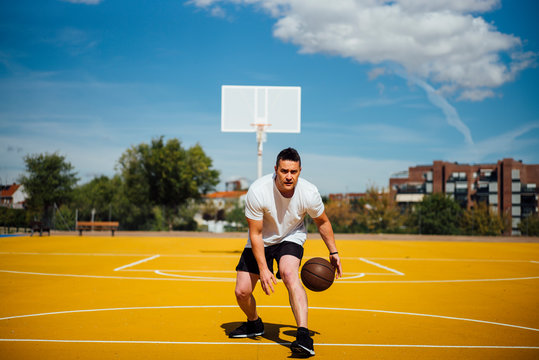 Man playing basketball on yellow court, dribbling