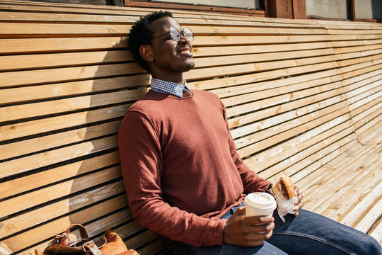 Young man sitting on wooden bench, eating hamburger, drinking coffee