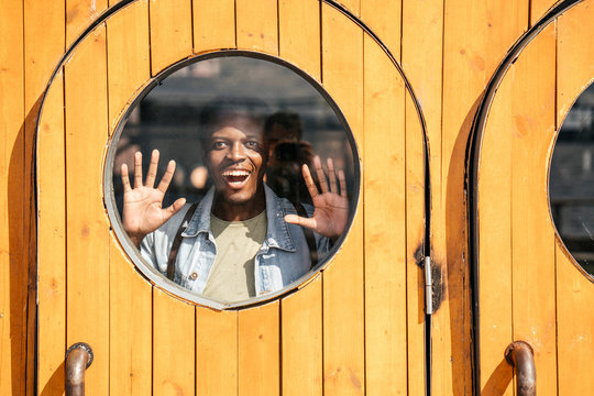 Young man behind wooden door, looking amazed through round window