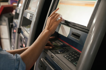 Young female traveller buying ticket from automated machine at station
