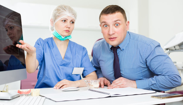 Female dentist explaining diacrisis to shocked man