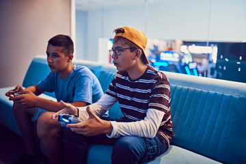 Teenage friends playing video game in an amusement arcade
