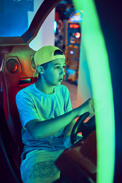Teenage boy playing with a driving simulator in an amusement arcade