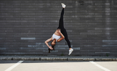 Doing crazy parkour and athletic stunts. Young sportive brunette with slim body shape against brick wall in the city at daytime