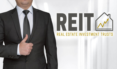 REIT Konzept und Geschäftsmann mit Daumen hoch