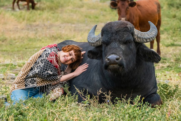 Tuinposter Buffel Young woman dressed in a poncho ride on big water buffalo