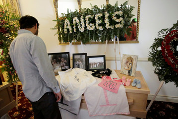 A person observes framed photographs of Rhonita Maria Miller and her four children, members of the Mexican-American Mormon community killed by unknown assailants, before her funeral in La Mora