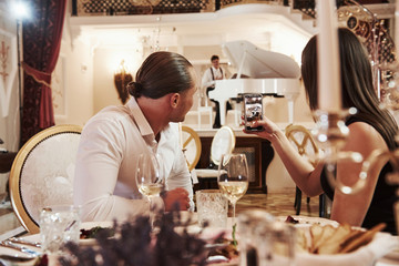 Conversation between pair and musician. Beautiful couple have romantic dinner in luxury restaurant at evening time
