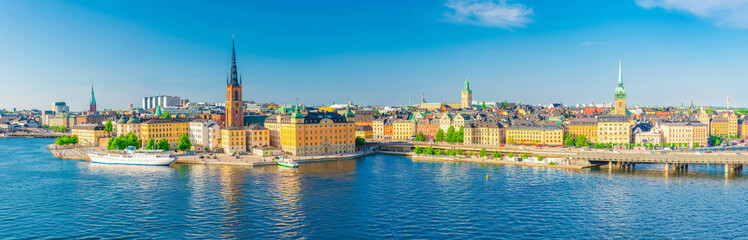 Aerial scenic panoramic view of Stockholm skyline with Old town Gamla Stan, typical Sweden houses, Riddarholmen island with gothic Church building, Lake Malaren, clear blue sky background, Sweden