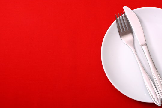 empty plate with fork and knife on red