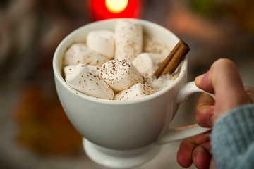 Girl hand holding hot chocolate with marshmallows
