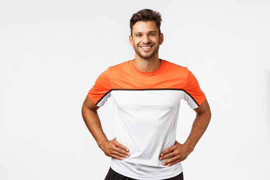 Fitness, sports and active lifestyle concept. Studio portrait handsome young male trainer in activewear, hold arms on waist, smiling friendly and determined, get your head in game, ready to workout