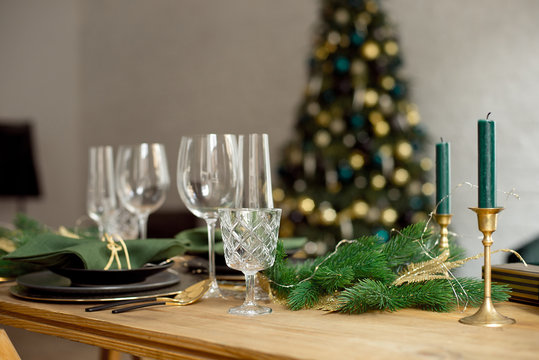 Christmas decoration with pine branches, table setting and candles on a dark Christmas tree background.