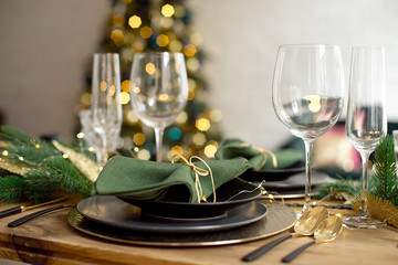 Table served for Christmas dinner in living room, close-up view, table setting, Christmas decoration.