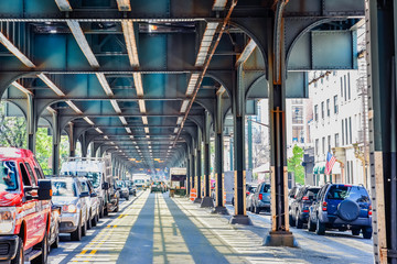 Foto auf Leinwand New York Bottom view of Elevated train track nyc. Traffic waiting in road in a sunny day. Travel and traffic concepts. Bronx, NYC, USA