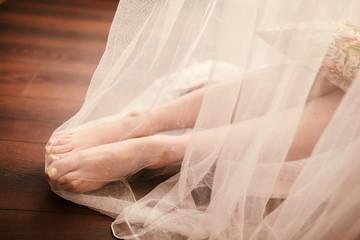 Bride morning preparation. Bride legs in white veil on wooden floor.