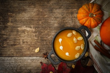 Homemade pumpkin soup on wooden autumn background